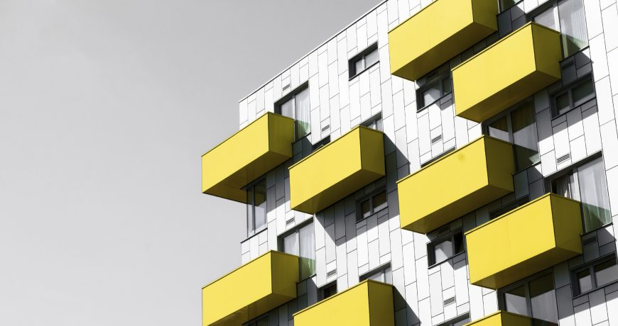 Modern apartments with balconies set against a blue sky